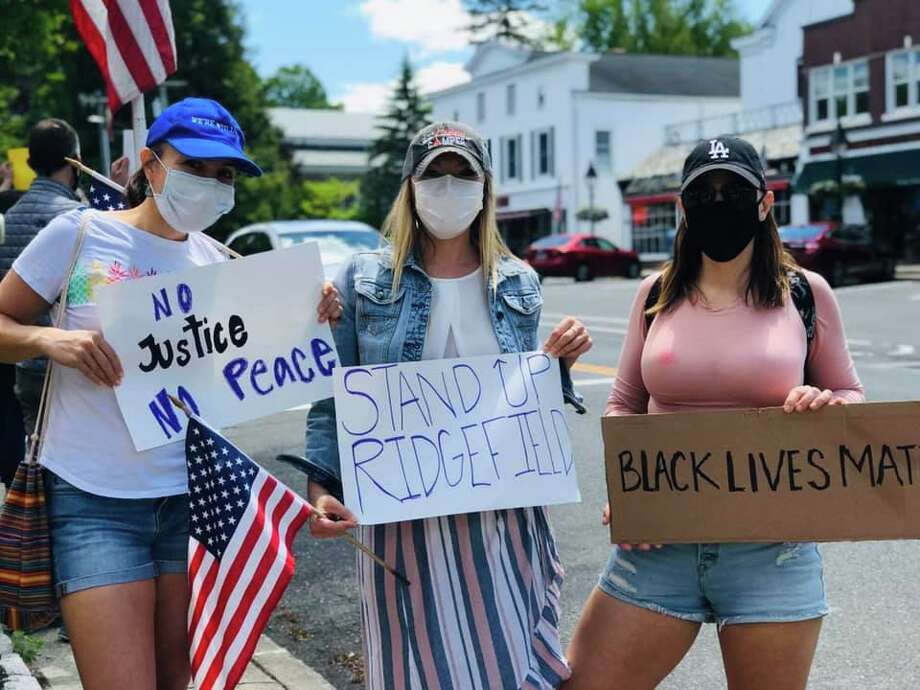 """No Justice No Peace"", ""Stand up Ridgefield"" and ""Black lives matter"" say signs at the protest in front of town hall last Sunday. Photo: Contributed Photo"