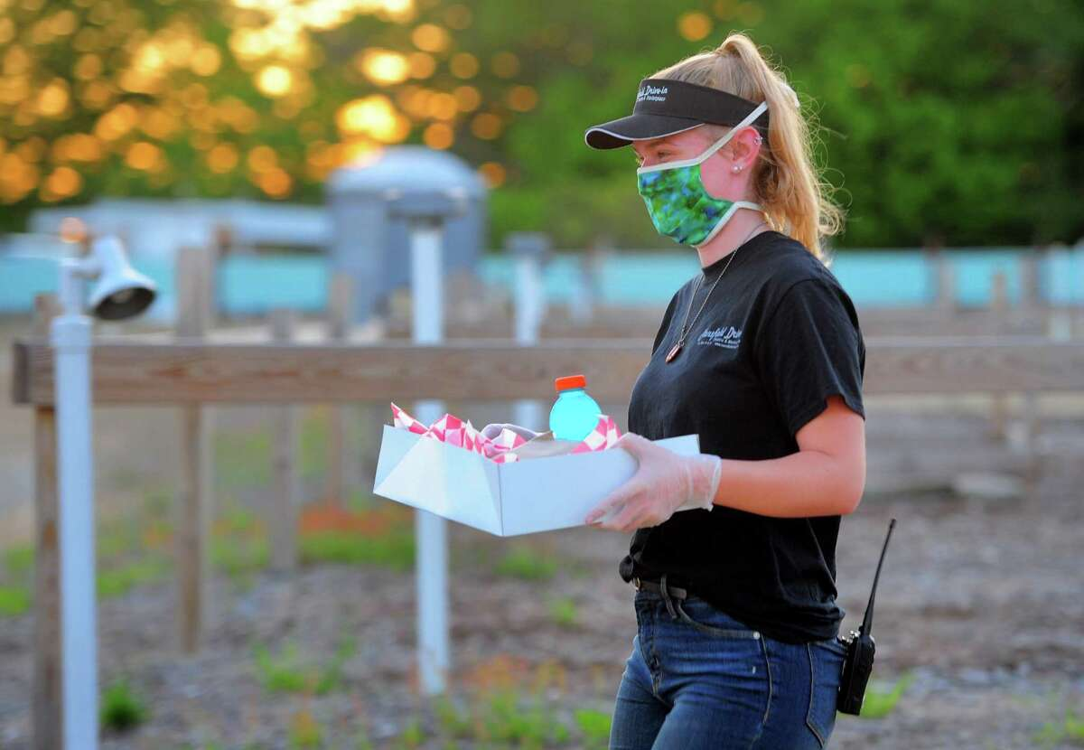 Mansfield Drive-In Movie Theater employee Kate McNeal delivers a customer's food order in Mansfield, Conn., on Tuesday May 26, 2020. Because of the coronavirus, the snack bar is staying closed and patrons order food online and it is brought to their cars.