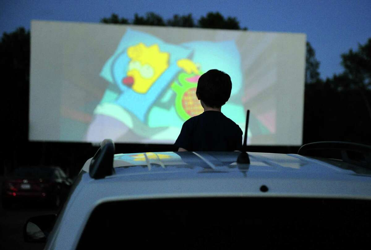 Patron William Rhines, 7, of Conventry enjoys a Simpson's cartoon before the Disney movie Onward at Mansfield Drive-In Movie Theater in Mansfield, Conn., on Tuesday May 26, 2020. Movie theaters and other entertainment venues will be capped at 100 people.