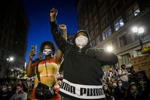 """Demonstrators raise their fists during a """"Sit Out the Curfew"""" protest against the death of George Floyd who died on May 25 in Minneapolis whilst in police custody, along a street in Oakland, California on June 3, 2020. - US protesters welcomed new charges against Minneapolis officers in the killing of African-American man George Floyd -- but thousands still marched in cities across the country for a ninth straight night, chanting against racism and police brutality. (Photo by Philip Pacheco / AFP) (Photo by PHILIP PACHECO/AFP via Getty Images)"""