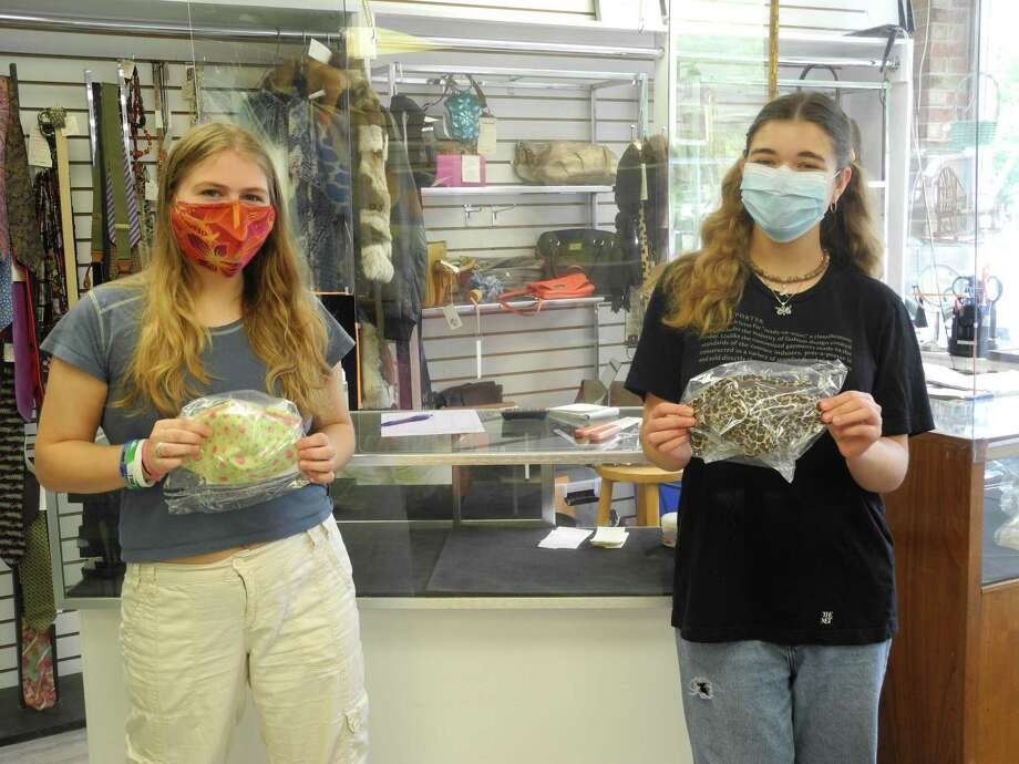 Nicole LaVorgna, left, and Eve Ogdon show off the face coverings for sale at the Turnover Shop in Wilton, CT, made by shop volunteer Janel Cassara. Both are 2018 Wilton High School graduates. LaVorgna is home for the summer from Endicott College, Ogdon from Tufts University. Photo: Jeannette Ross / Hearst Connecticut Media / Wilton Bulletin