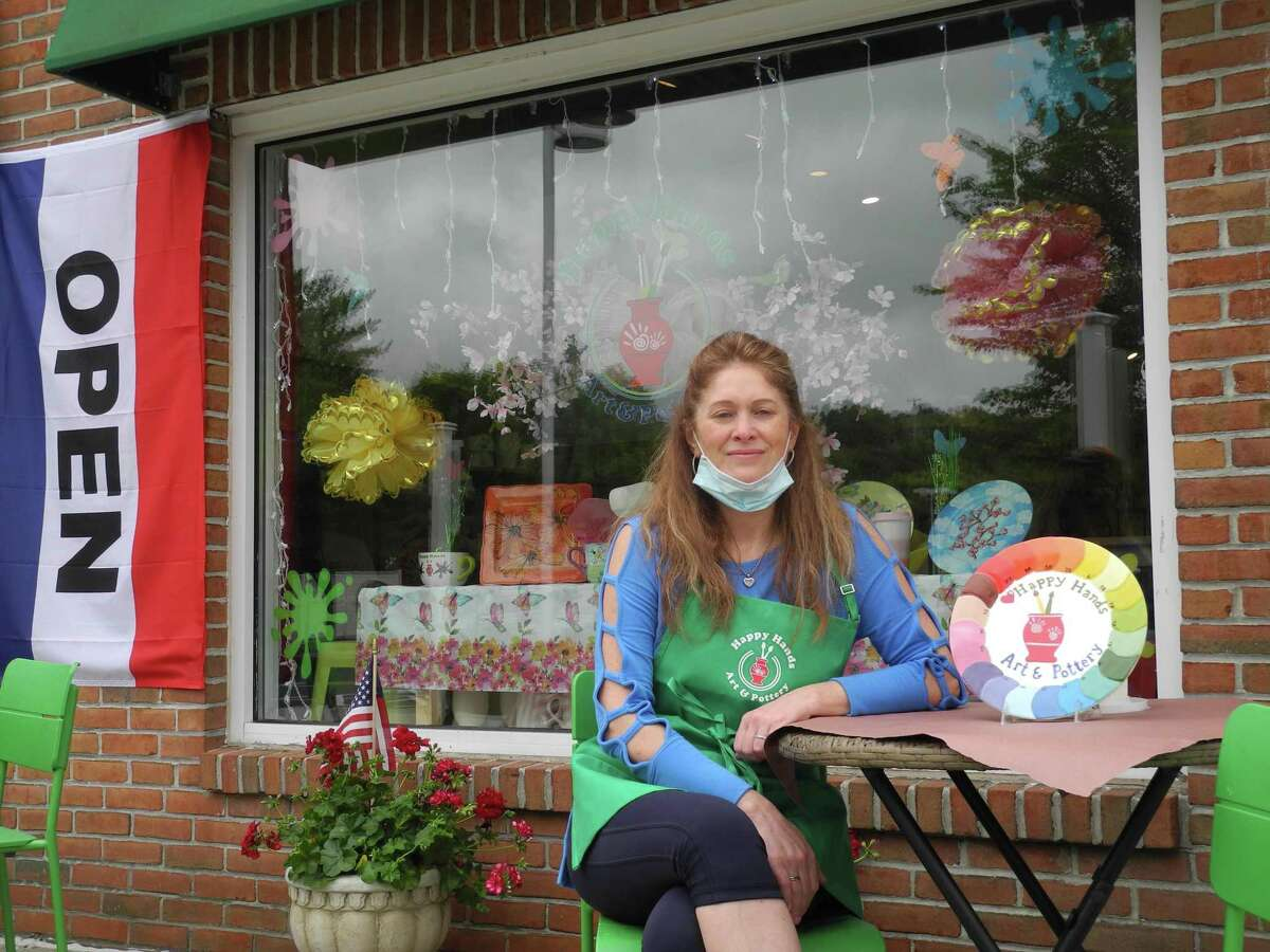 Happy Hands Pottery owner Alla Ionescu sits at one of the tables now outside her studio in Wilton after it reopened May 22.
