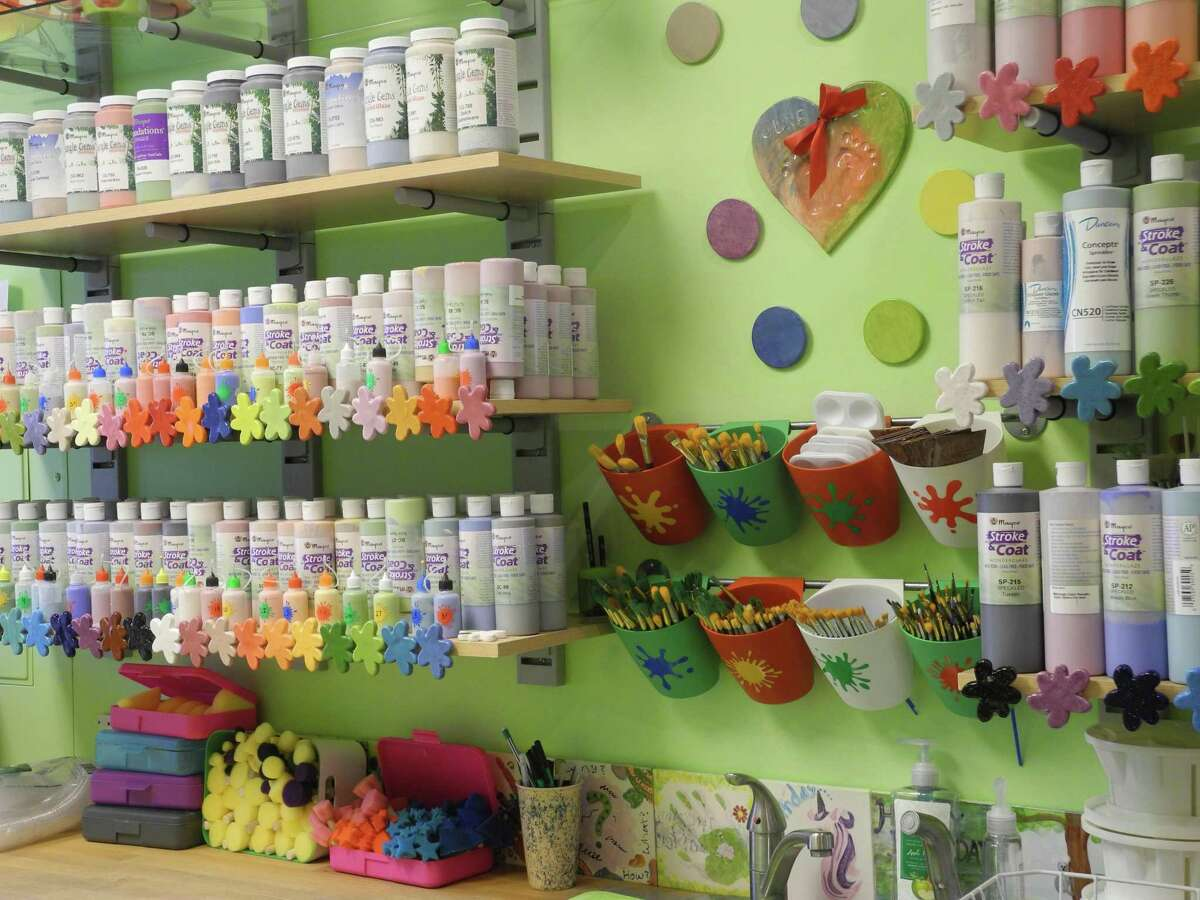 Paints and brushes line the wall at Happy Hands Pottery in Wilton after the store reopened May 22.