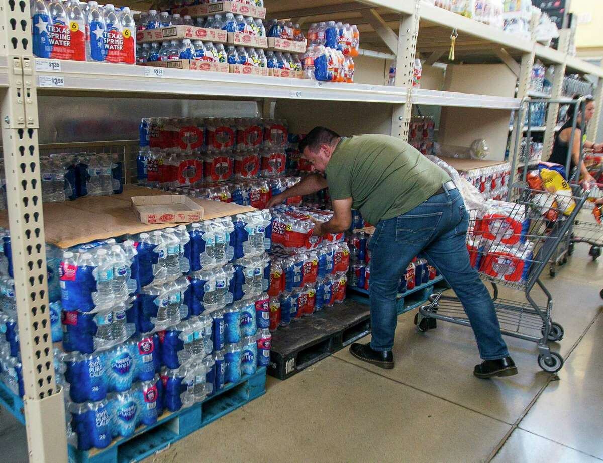 You can stock up on supplies all year-round to avoid getting stuck without when a storm hits. Fernando Lorenzo grabs four cases of water at the Montrose Market H-E-B on West Alabama Street during his lunch break, Wednesday, July 10, 2019.