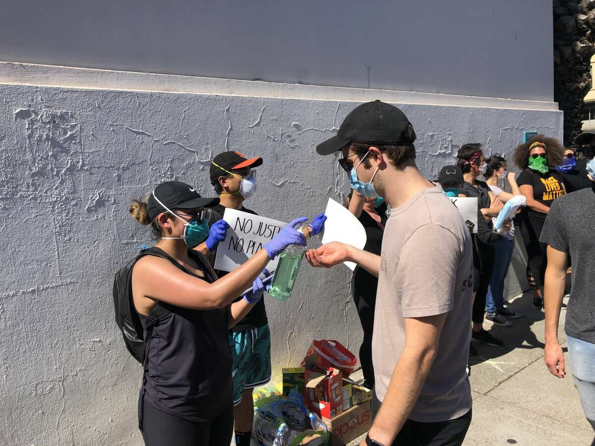 """""""I want to be here as long as I can but my shift at Kaiser starts at eleven!"""" Cavetano said as she helped clean the hands of grateful demonstrators passing by.Around the corner on 18th Street students Thu Tran and Melanie Tamayo manned a makeshift station of water bottles, masks, milk and medical supplies alongside a sign that read """"Take what you need."""""""