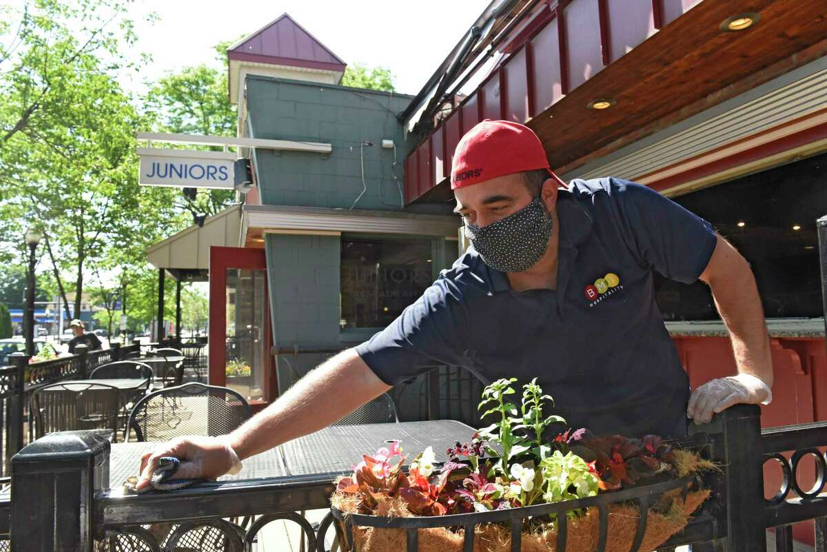 Brian Viglucci, co-owner of Juniors, cleans and sets up for outdoor dining which reopens today on Thursday, June 4, 2020 in Albany, N.Y. (Lori Van Buren/Times Union)