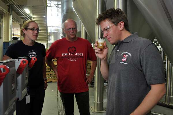 Sacred Heart biology professors Geffrey Stopper, right, and Kirk Bartholomew at Two Roads Brewing Co. with Kendra Frederick, former director of quality assurance at the brewery. (August 2013)