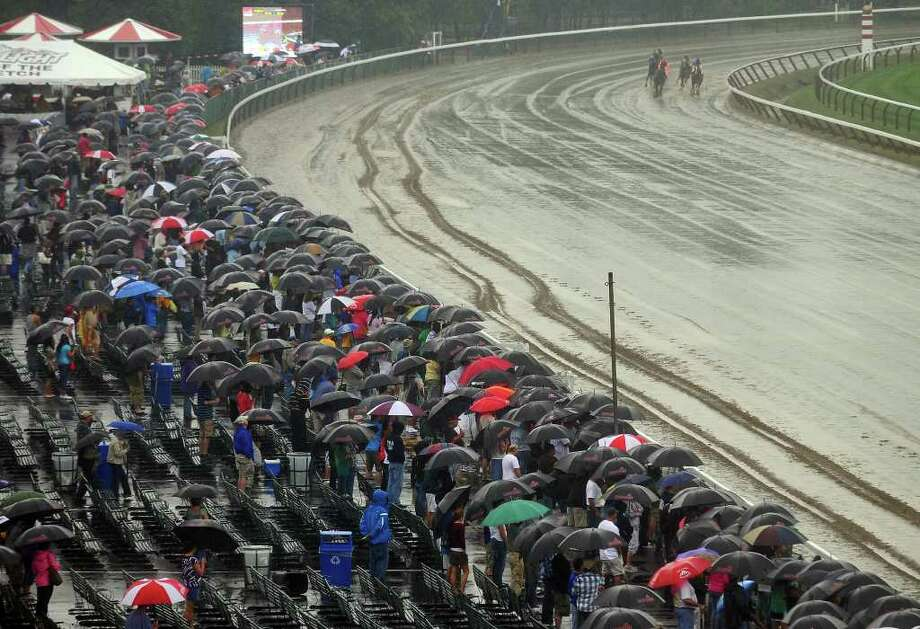 Horses head to the finish line during the second race at  Saratoga Race Course  in Saratoga Springs, NY  on a rainy Sunday August 22,  2010.  Umbrellas were the giveaway of the day. ( Philip Kamrass / Times Union ) Photo: Philip Kamrass