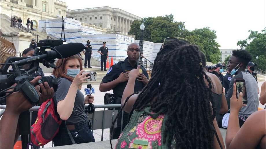 A U.S. Capitol Police officer identified as R. Watts explains to protesters Wednesday evening why he wears a badge. Photo: Washington Post Photo By John Woodrow Cox / The Washington Post