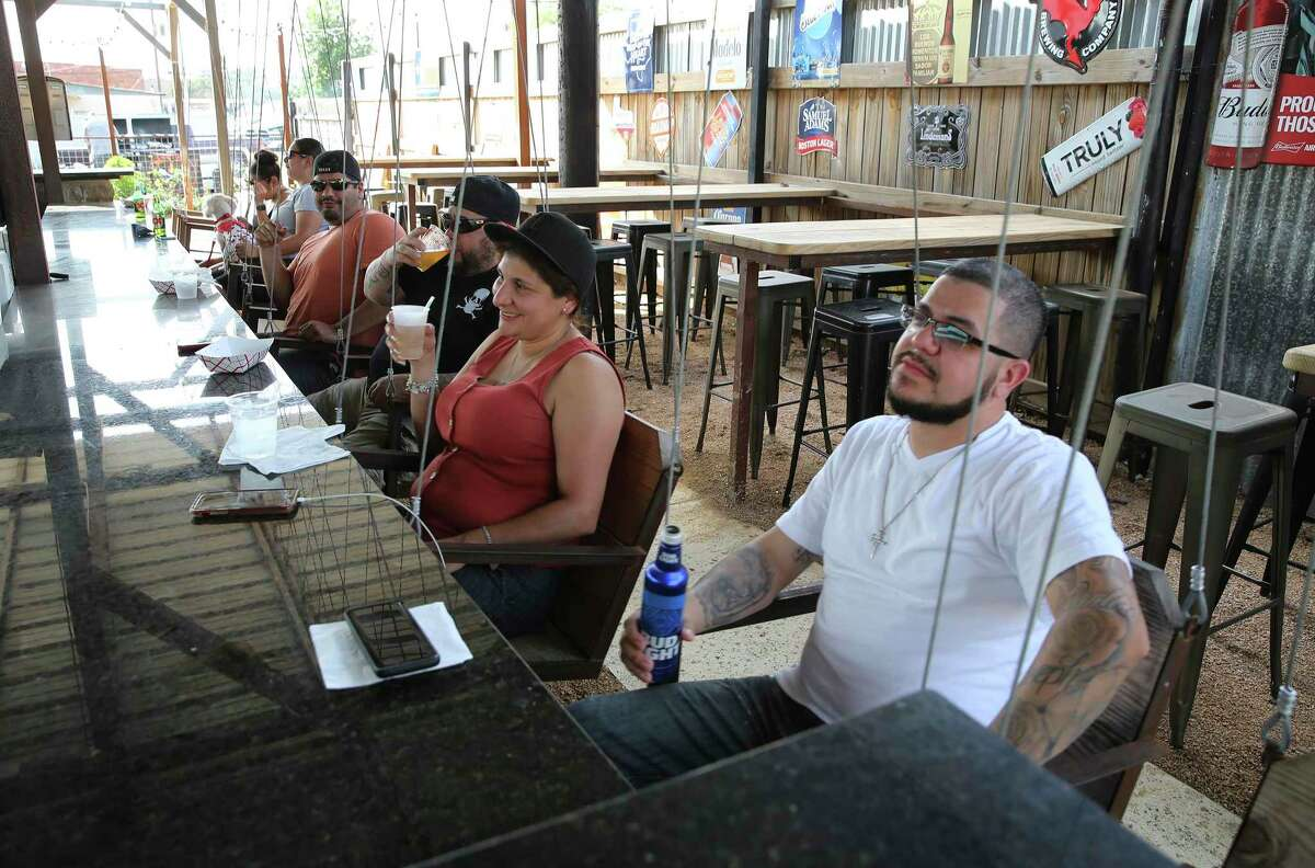 Patrons at Bentley's Beer Garden relax on swings as bars in San Antonio as well as across Texas reopen on Friday, May 22, 2020. State rules for their re-opening require them to operate at 25 percent capacity, have patrons sit at tables with a six per person limit and dancing or other close-contact is discouraged.