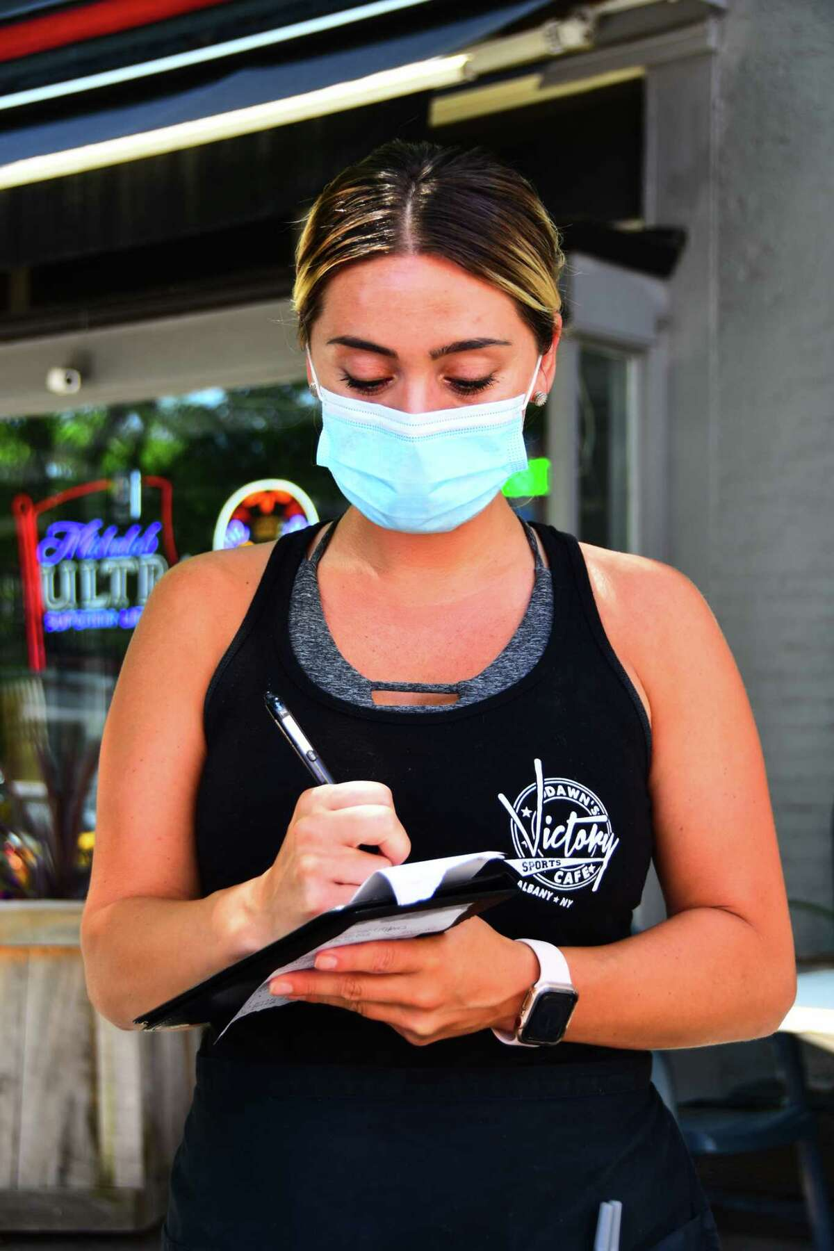Summer Waterhouse, a server at Dawn's Victory Sports Cafe in Albany, on her first day back at work Thursday after more than 11 weeks of a coronavirus-related furlough.
