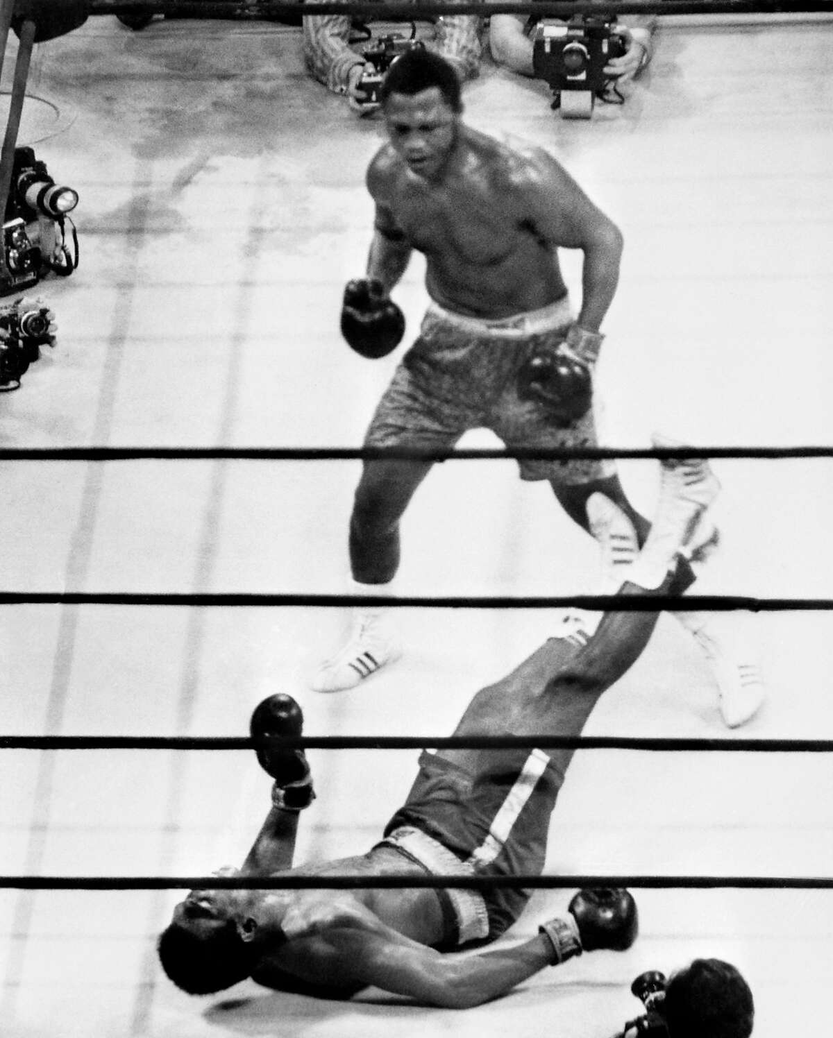 (FILES) This file picture taken on March 8, 1971 shows US heavyweight boxing champion Joe Frazier (top) standing over compatriot Muhammad Ali as he wins the fight called the