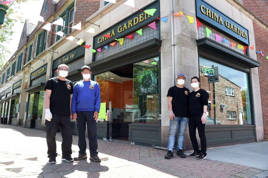 The China Garden owners Ling Dong, right, and her husband, Zhi Chen, are photographed in front of their recently opened takeout restaurant on Main Street in Branford on May 22, 2020, with Yi Chen, left, and Seng Ng, far left. Photo: Arnold Gold / Hearst Connecticut Media / New Haven Register
