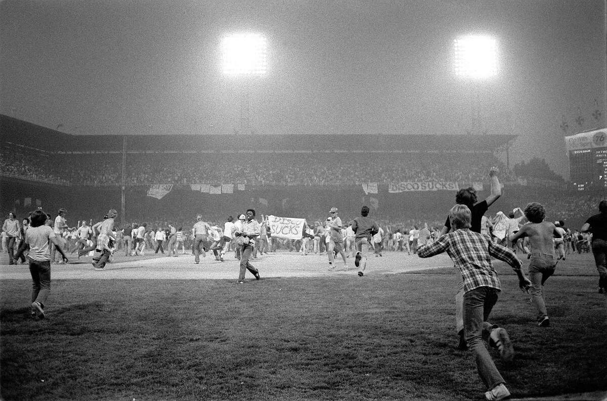 Fans storm the field at Chicago's White Sox Park on Disco Demolition night Thursday, July 12, 1979 after the first game of a double header between the White Sox and Detroit Tigers. The promotion by a local radio station turned into a melee after hundreds of disco records were blown up on the field. The second game of the double header was called by umpires who declared the field unfit for play. (AP Photo/Fred Jewell)