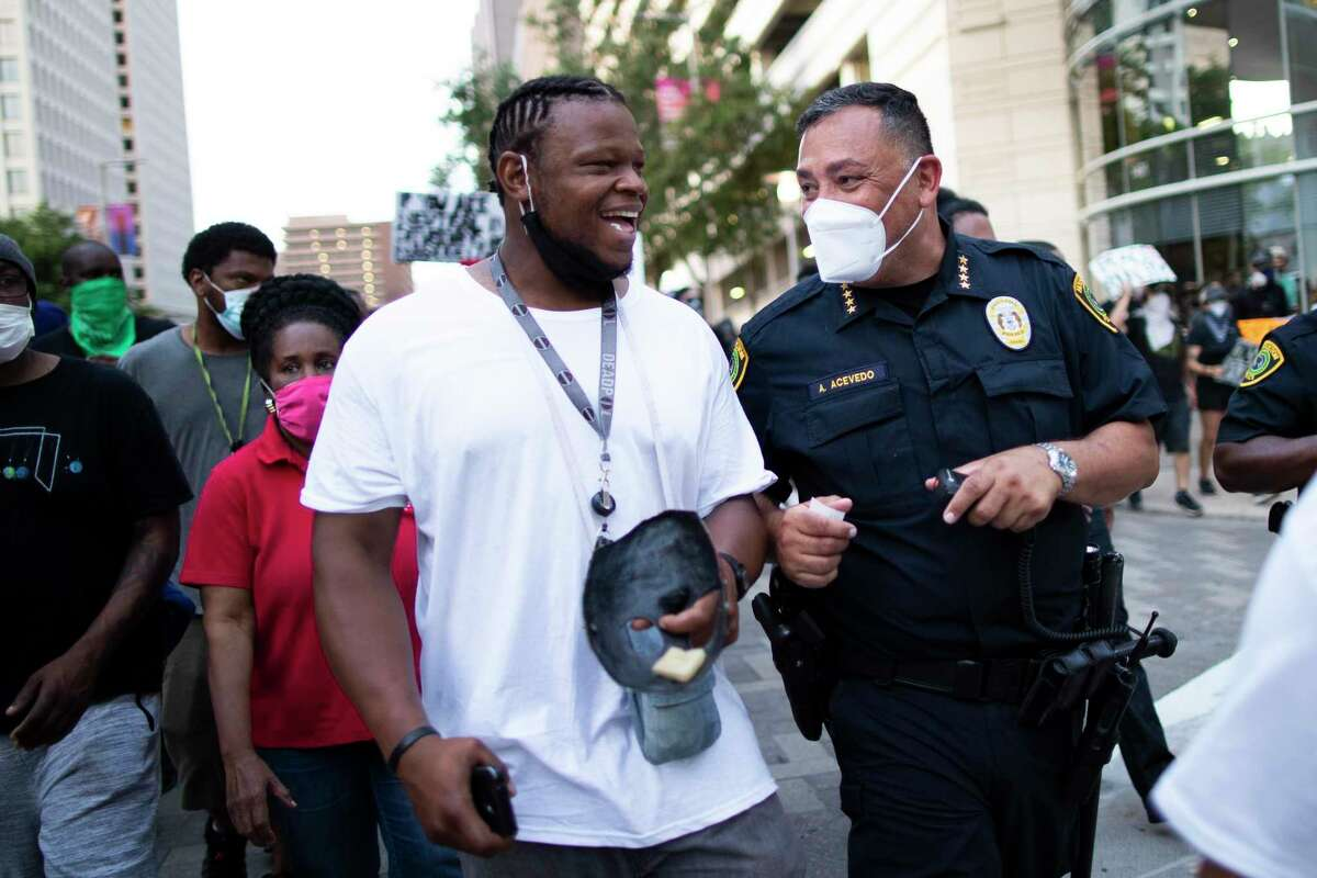Houston Police Chief Art Acevedo talks to a protester during a march in downtown Houston on Saturday, May 30. The demonstrators protested against the death of George Floyd while in custody of police in Minneapolis.
