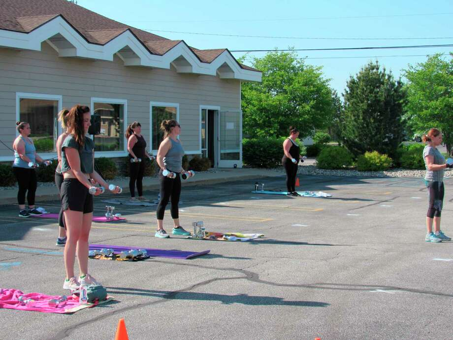 People work out on Wednesday in the parking lot of Seung-ni Fit Club in Midland. The gym began hosting outdoor classes to the general public on Tuesday, a day after Gov. Whitmer lifted her stay at home order and allowed fitness facilities to provide outdoor classes. (Victoria Ritter/vritter@mdn.net)