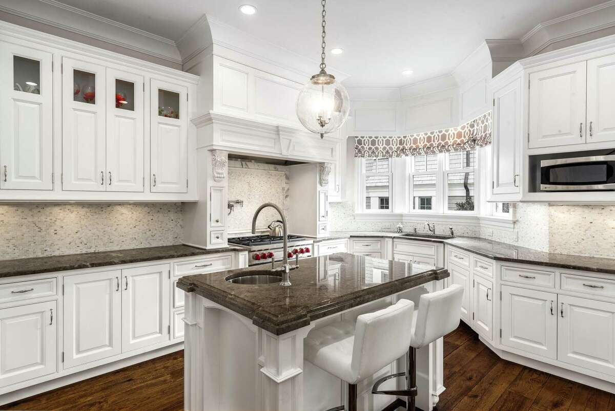 The kitchen is naturally the hub of the 4,406-square-foot home, with cabinets finished in a matte white. There are two sinks, and among the appliances are a Wolf range and oven, a Miele coffee station and dishwasher, and Sub-Zero refrigerator and freezer.