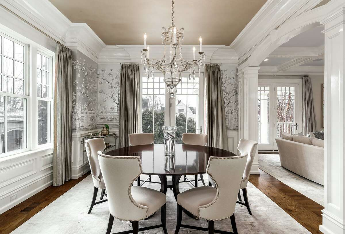 The formal dining room is also a lovely space for entertaining in style. The ceiling is finished in gold leaf, and the walls are swathed in Gracie-designed wallpaper and customized by an artist who incorporated four pairs of lovebirds into the design.
