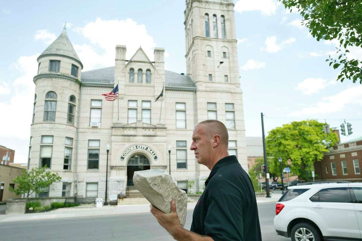 Cohoes Mayor Bill Keeler holds a large piece of stone that fell off the bell tower section of the Cohoes City Hall roof, seen in the background, on Thursday, June 4, 2020, in Cohoes, N.Y. (Paul Buckowski/Times Union)