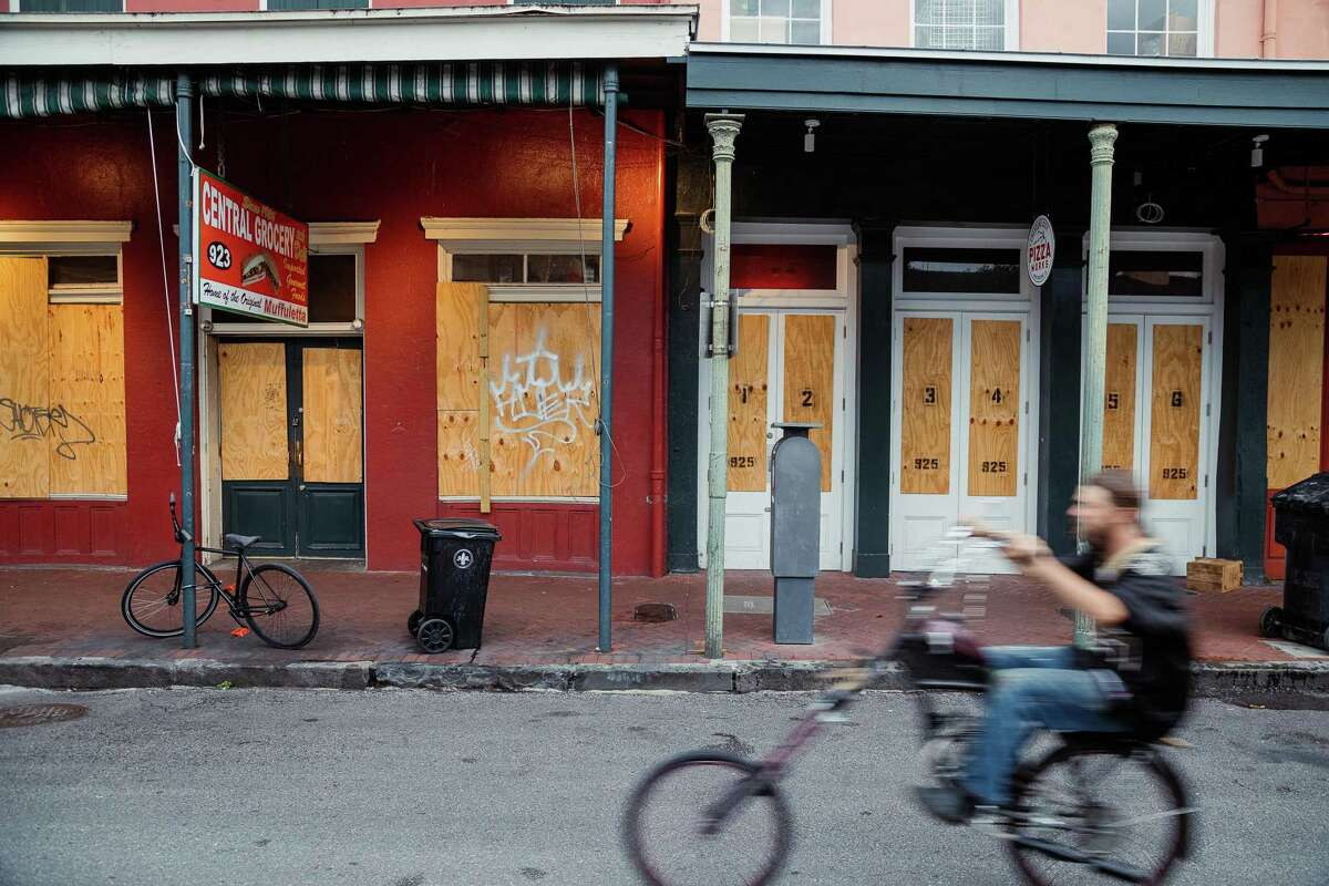 A cyclist rides past shops temporarily closed in the French Quarter neighborhood of New Orleans.