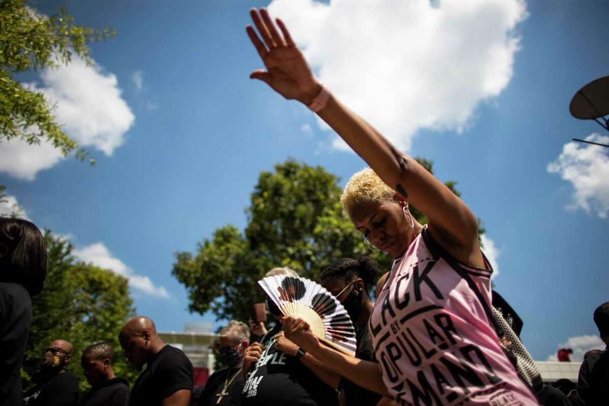 A woman extends her hand as she joins protestors in prayer in a march on Tuesday, June 2, 2020, at the Discovery Green in downtown Houston.
