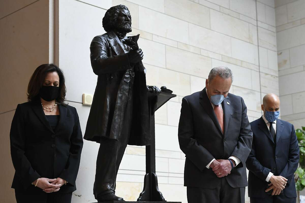 Standing near a statue of Frederick Douglass, Sen. Kamala Harris, D-Calif., left, Senate Minority Leader Sen. Chuck Schumer of N.Y., center, and Sen. Cory Booker, D-N.J., right, pause during a prayer Capitol Hill in Washington, Thursday, June 4, 2020, during an event to commemorate the life of George Floyd, who died after being restrained by Minneapolis police officers. (AP Photo/Susan Walsh)