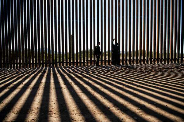 U.S. Border Patrol agents look at the border fence construction in Lukeville, Arizona.