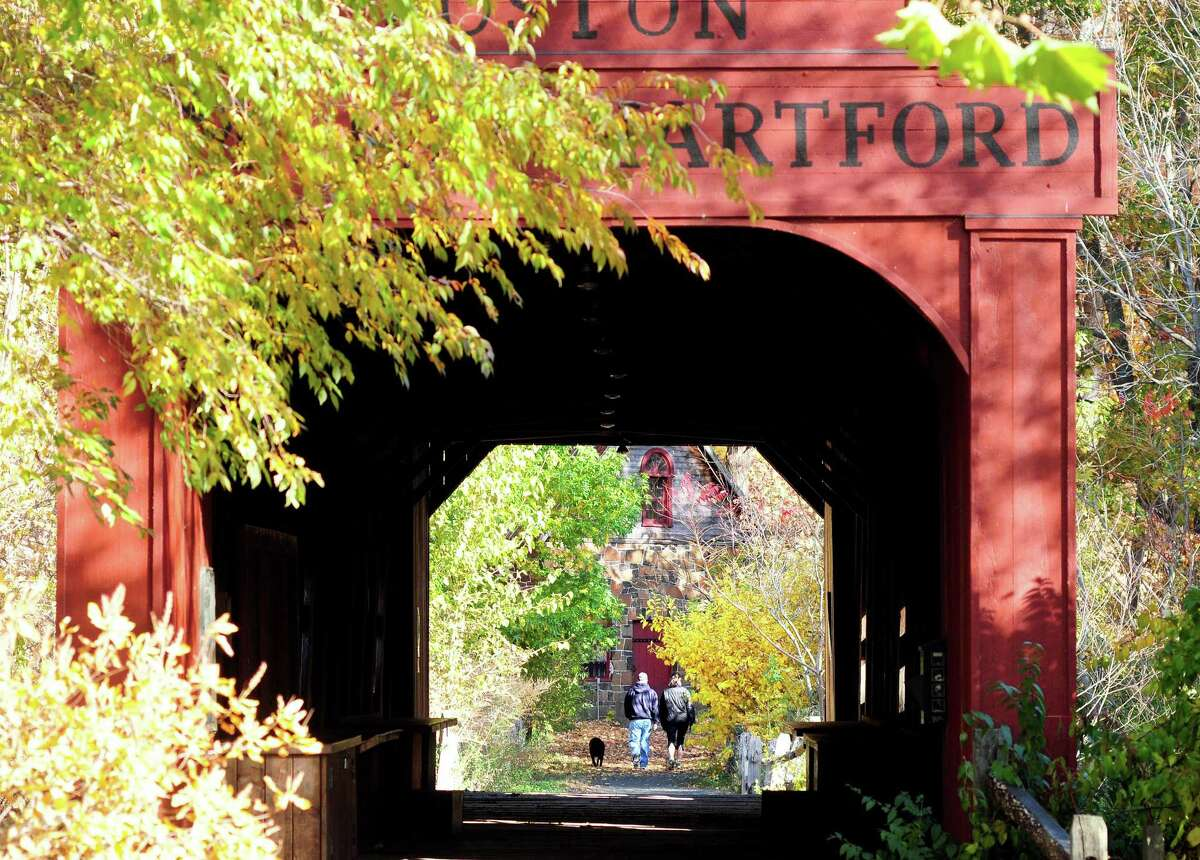 A couple walks a dog into East Rock Park past a covered bridge next to the Eli Whitney Museum in Hamden, which offers an online program these days.