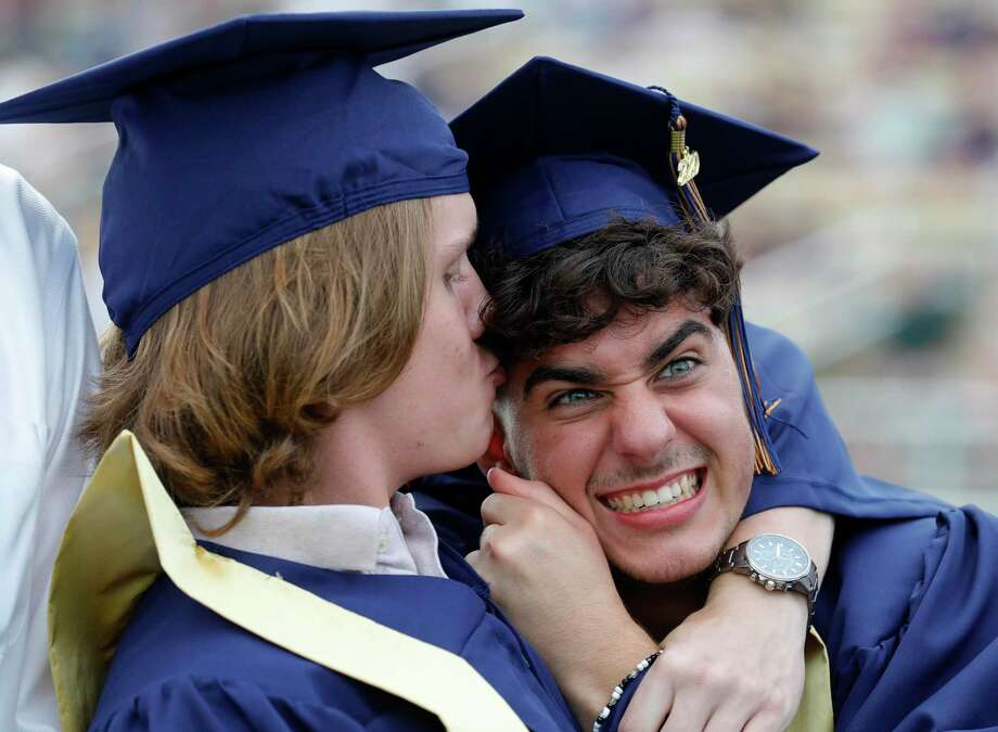 Landen Grayless, center, reacts as Dylan Hewczuk pulls him in for a kiss before a graduation ceremony for Lake Creek High School at MISD Stadium, Thursday, June 4, 2020, in Montgomery. The 220 students in the school's inaugural graduating class attended the outdoor ceremony with social distancing and other safety guidelines. Photo: Jason Fochtman, Houston Chronicle / Staff Photographer / 2020 © Houston Chronicle