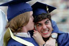 Landen Grayless, center, reacts as Dylan Hewczuk pulls him in for a kiss before a graduation ceremony for Lake Creek High School at MISD Stadium, Thursday, June 4, 2020, in Montgomery. The 220 students in the school's inaugural graduating class attended the outdoor ceremony with social distancing and other safety guidelines.