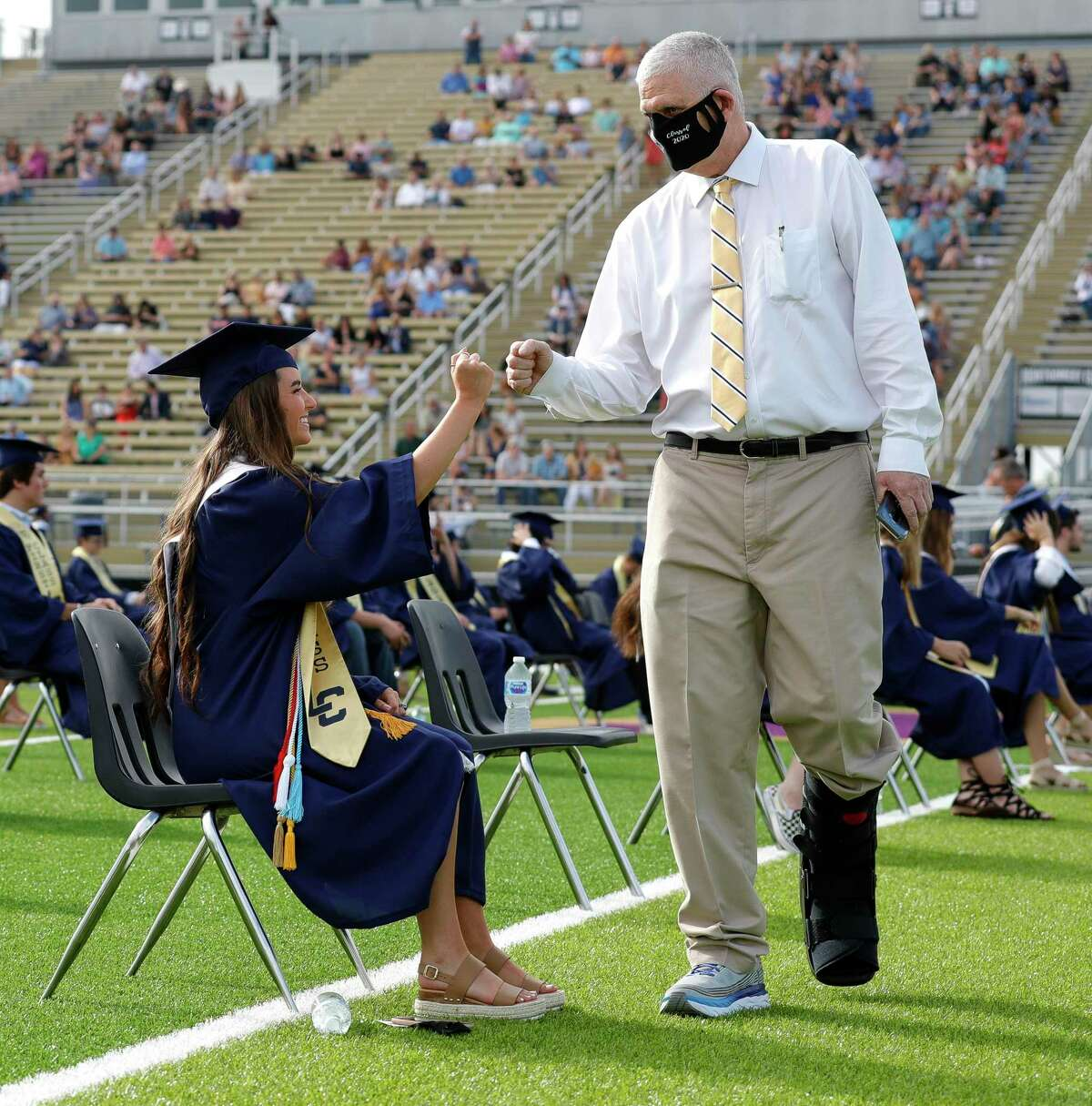 Lake Creek Principal Phil Eaton, right, gives a fist-bump to Reagan Cole before a graduation ceremony for Lake Creek High School at MISD Stadium, Thursday, June 4, 2020, in Montgomery. Eaton contracted and surived COVID-19 after a 51-day battle with the virus. The 220 students in the school's inaugural graduating class attended the outdoor ceremony with social distancing and other safety guidelines.
