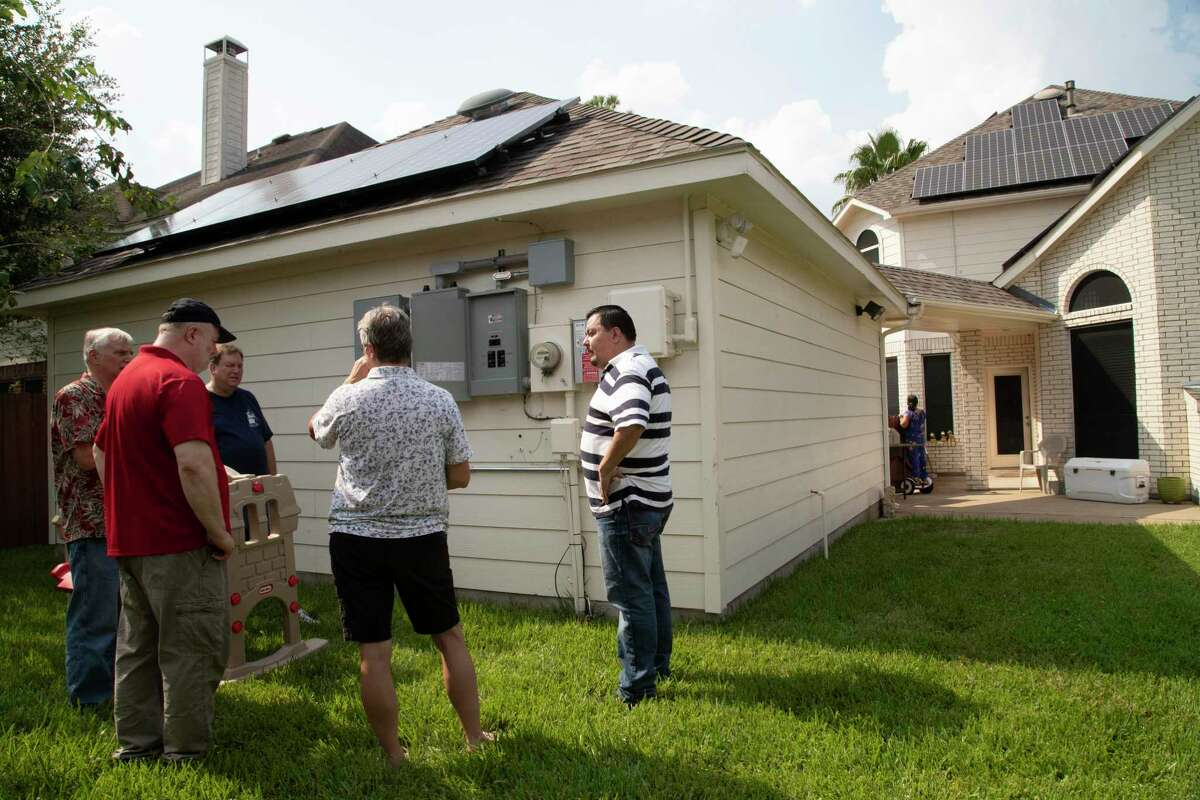Jose Flores, center, gives a solar power tour of his home on Saturday, Oct. 5, 2019, in Clear Creek.