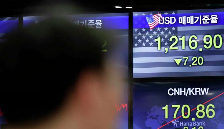 A currency trader works near the screens showing the foreign exchange rates at the foreign exchange dealing room in Seoul, South Korea, Thursday, June 4, 2020. Asian stock markets are mixed after Wall Street rose on better U.S. jobs and manufacturing data than expected. (AP Photo/Lee Jin-man)