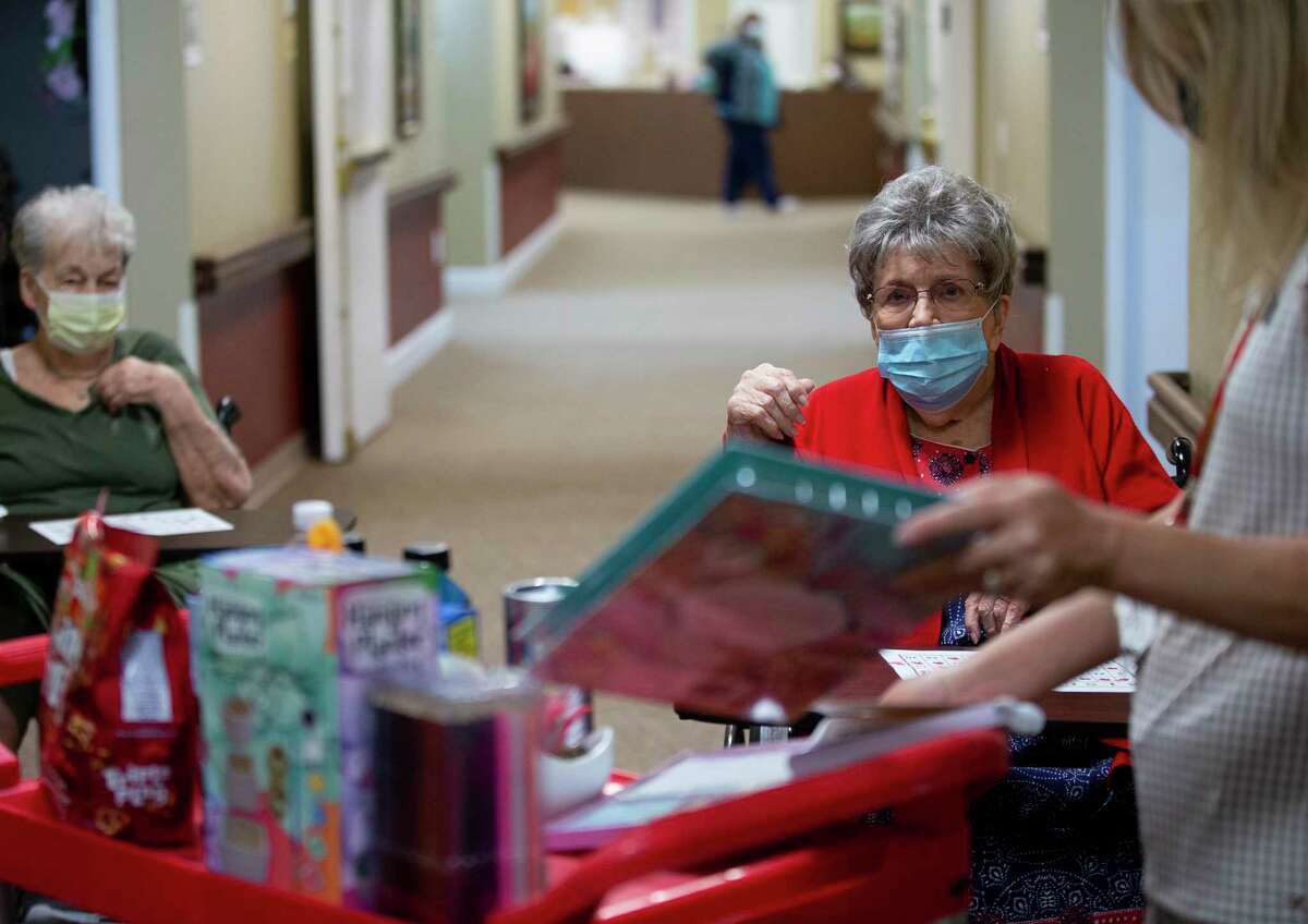 Lilian McNeill, 85, looks at the prize cart after completing a column while playing Bingo at the Bayou Pines Care Center on Wednesday, June 3, 2020, in La Marque, Texas. The staff hold bingo nights Mondays, Wednesdays, and Saturdays in an effort to help residents feel less isolated and alone as they remain stuck in their rooms.