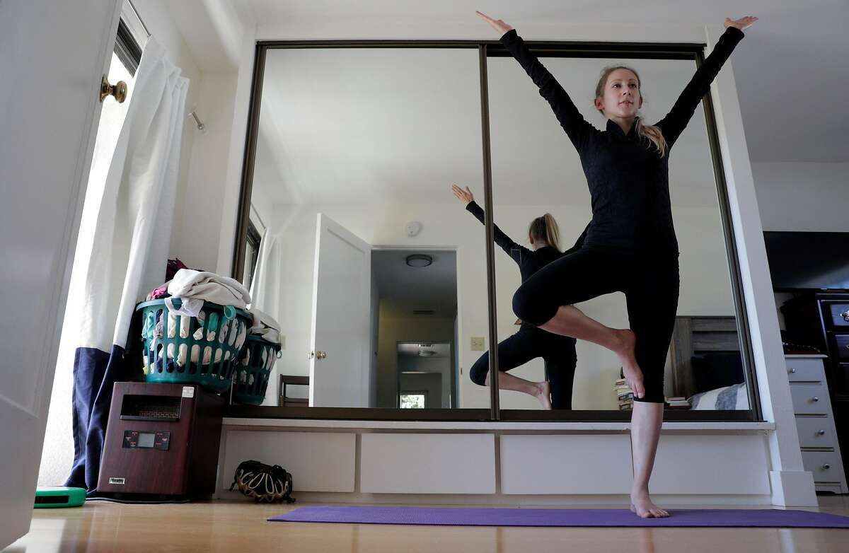 Erica Sladky, who was laid off from her job as a biotech engineer because of the COVID-19 pandemic, does a yoga pose in Berkeley, Calif., on Monday, June 1, 2020. Sladky spends her time job hunting, practicing her yoga, and walking Oreo.