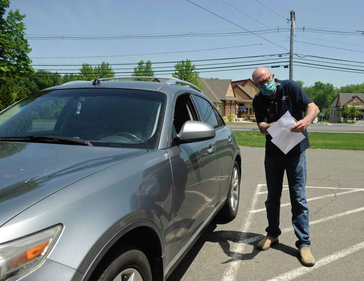 Dale Robertson, of Newtown Pools, explains the results of the pool and spa water test he performed to Elle Callanan, of Easton. Callanan was doing curbside pickup at the store, Thursday, May 4, 2020, in Newtown, Conn.