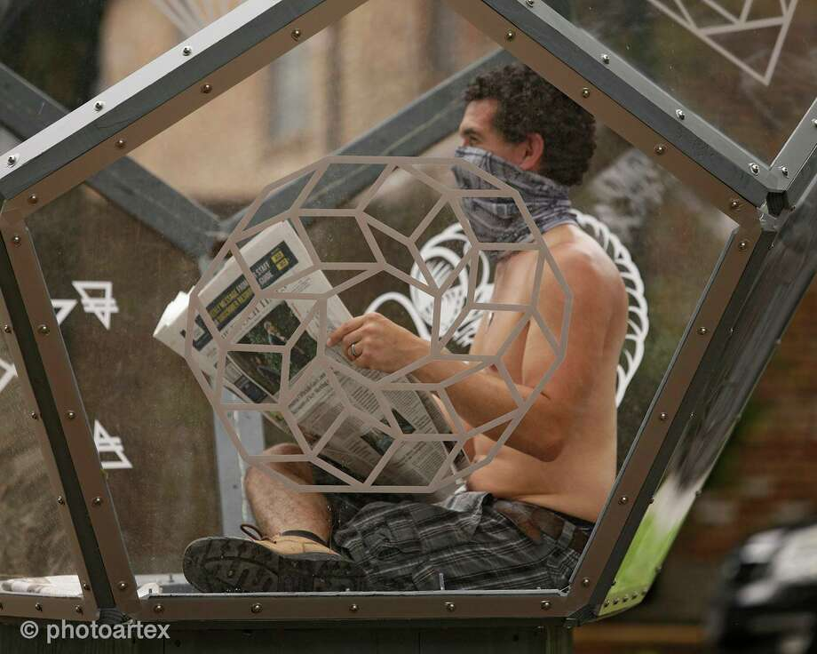 """In his """"Artist Self-Quarantine,"""" fine artist Vincent Fink reads a newspaper inside his Dodecahedron sculpture on Heights Boulevard in Houston as public performance art. The exhibit is a reflection on the isolation brought on by the COVID-19 pandemic. Photo: Photo ByWilliam Guaregua Photography"""