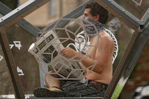 "In his ""Artist Self-Quarantine,"" fine artist Vincent Fink reads a newspaper inside his Dodecahedron sculpture on Heights Boulevard in Houston as public performance art. The exhibit is a reflection on the isolation brought on by the COVID-19 pandemic."