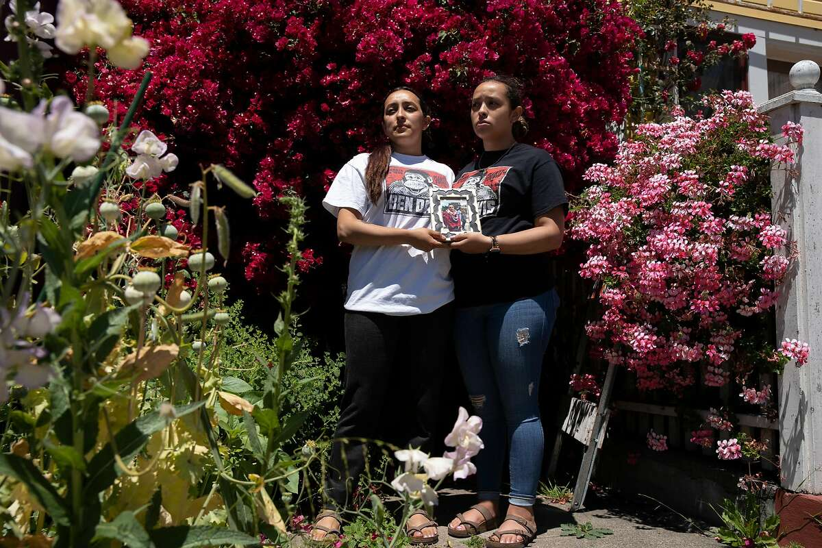 From left: Michelle Monterrosa and her sister Ashley Monterrosa hold a portrait of their brother Sean Monterrosa on Thursday, June 4, 2020, in San Francisco, Calif. Sean Monterrosa, 22, was fatally shot by Vallejo police. Sean was kneeling outside a Walgreens and not carrying a firearm when an officer opened fire � sending five bullets through his own windshield. Monterrosa, of San Francisco died after the shooting at around 12:30 a.m. Tuesday, but police did not tell the public the man was killed � or disclose the circumstances of the shooting � until Wednesday at a news conference outside City Hall, a day after calling in 50 troops from the National Guard to help control protests and rioting sparked by the Minnesota police killing of George Floyd.