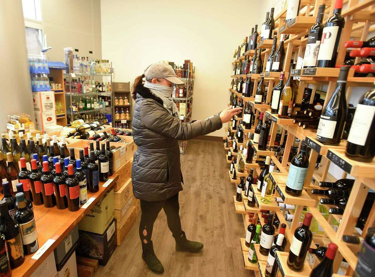 Suzie Frauenhofer of Stamford makes a selection of a wine at Harbor Wines & Spirits in Stamford April 24, 2020. Owner Terry Rogers has seen a change in her business, with many customers opting to purchase budget wines as they watch their family financial budgets during the COVID-19 crisis. She has tailored her wine selection, catering to her customer needs.