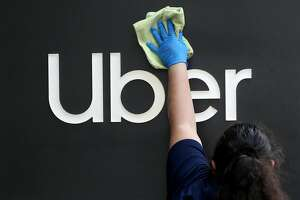 SAN FRANCISCO, CALIFORNIA - MAY 18: A worker cleans a sign in front of the Uber headquarters on May 18, 2020 in San Francisco, California. Uber announced plans to cut 3,000 jobs and shutter or consolidate 40 offices around the world due to severely declining business as the coronavirus (COVID-19) pandemic continues. The cuts come two weeks after Uber cut 3,700 employees. (Photo by Justin Sullivan/Getty Images)