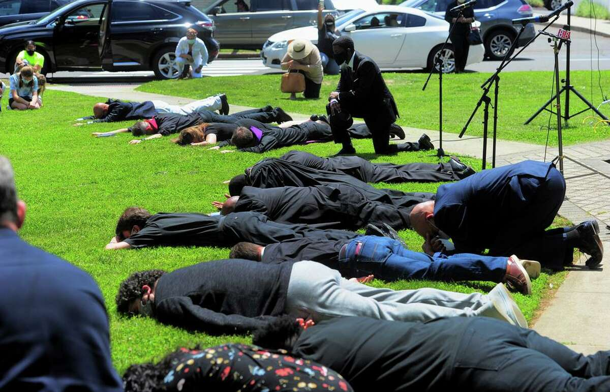Members of the Milford Clergy Association lie in the prone position for more than eight minutes Thursday, representing the time police held down George Floyd, during a prayer vigil on Milford Green. Around 50 people gathered with the clergy to pray for the country in light of the deepening racial tensions in the aftermath of the death in police custody of George Floyd in Minneapolis.