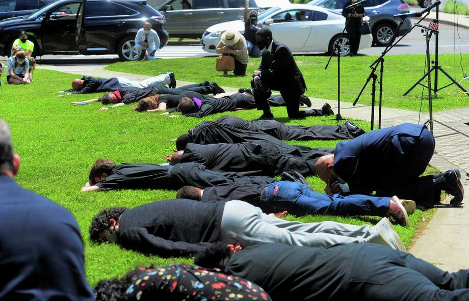 Members of the Milford Clergy Association lie in the prone position for more than eight minutes Thursday, representing the time police held down George Floyd, during a prayer vigil on Milford Green. Around 50 people gathered with the clergy to pray for the country in light of the deepening racial tensions in the aftermath of the death in police custody of George Floyd in Minneapolis. Photo: Christian Abraham / Hearst Connecticut Media / Connecticut Post