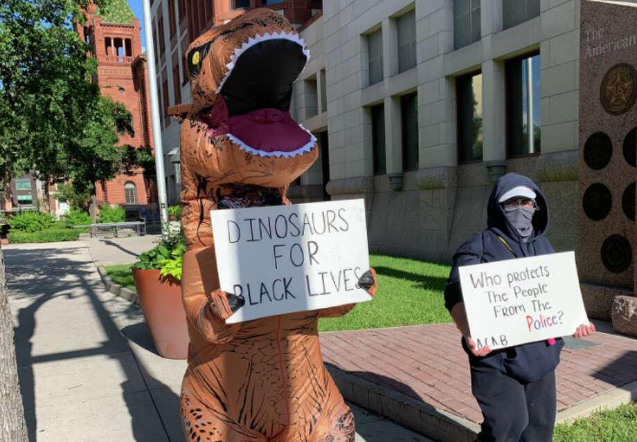 A protester dressed as a dinosaur attends a protest in San Antonio. Photo: Silvia Foster-Frau