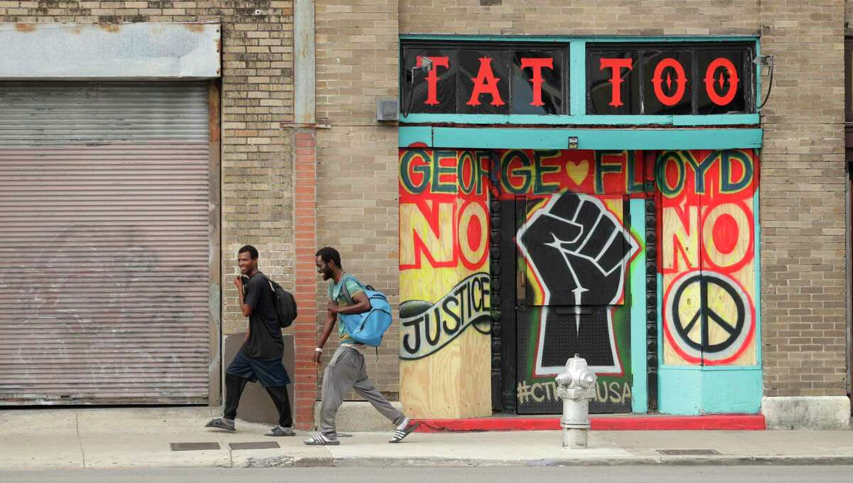 Two men pass a boarded up business with a message and mural in San Antonio, Thursday, June 4, 2020, referring to the death of George Floyd, a black man who was in police custody in Minneapolis. Floyd died after being restrained by Minneapolis police officers on Memorial Day. (AP Photo/Eric Gay)