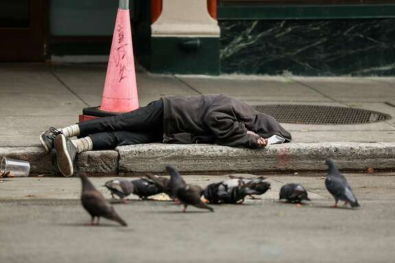 A person sleeps on the sidewalk outside of Curtis Bradford�s apartment building on Sunday, May 31, 2020 in San Francisco, California.
