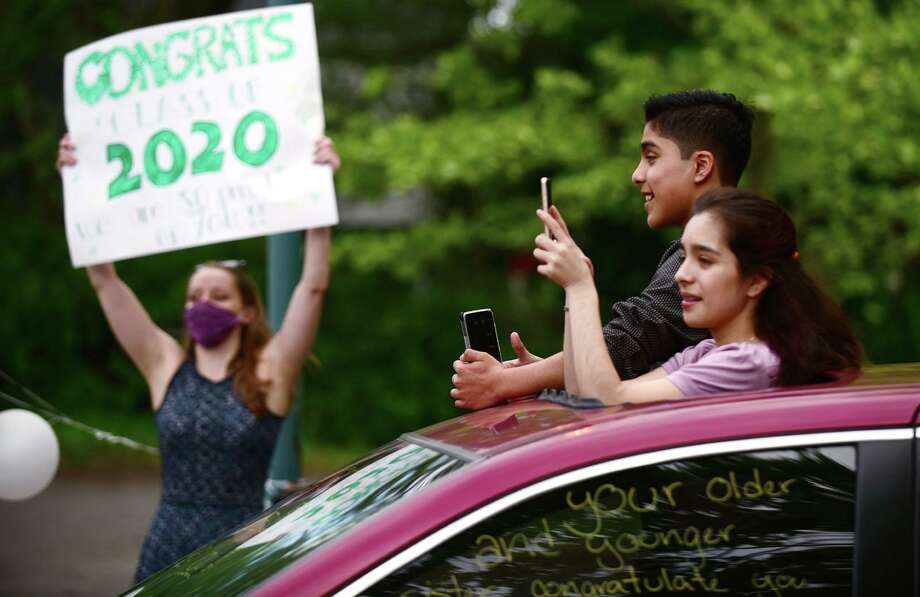 8th grade students from West Rocks Middle School receive congratulations from the staff Thursday, June 4, 2020, during a drive-thru graduation ceremony at the school in Norwalk, Conn. Photo: Erik Trautmann / Hearst Connecticut Media / Norwalk Hour