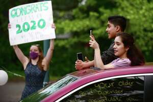 8th grade students from West Rocks Middle School receive congratulations from the staff Thursday, June 4, 2020, during a drive-thru graduation ceremony at the school in Norwalk, Conn.