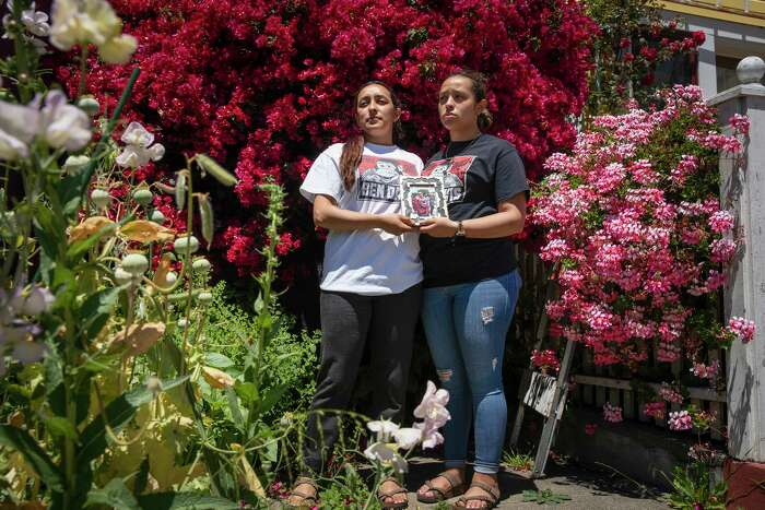 From left: Michelle Monterrosa and sister Ashley hold a portrait of brother Sean in San Francisco. Sean was fatally shot by