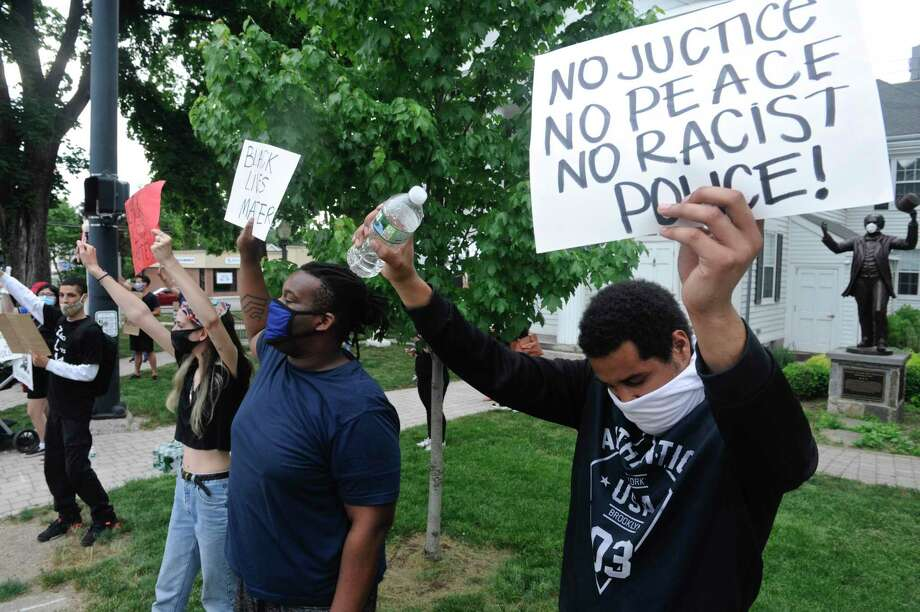 Jay, right, who preferred not to use his last name, and Marcus Willis, of Torrington, hold up a signs during a protest in Bethel on Friday evening. Due to coronavirus concerns a candlelight vigil, for justice in the wake of the death of George Floyd, in front of the municipal center was postponed. People gathered anyway in front of the Bethel Library. Thursday evening, June 4, 2020, in Bethel, Conn. Photo: H John Voorhees III / Hearst Connecticut Media / The News-Times